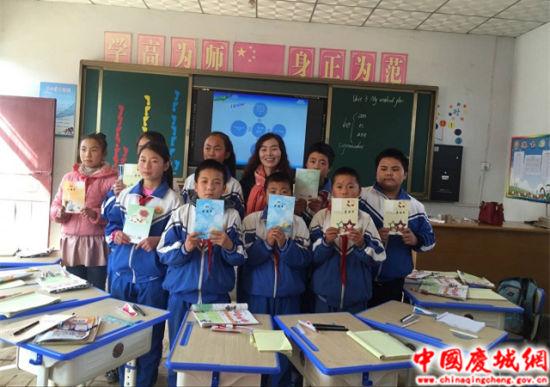 葛崾岘高庙教育点学生手捧教师送来的礼物与教师一同合影
