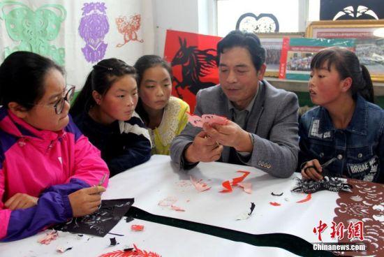 李敏贤教孩子们剪纸技艺。郭惠民 摄
