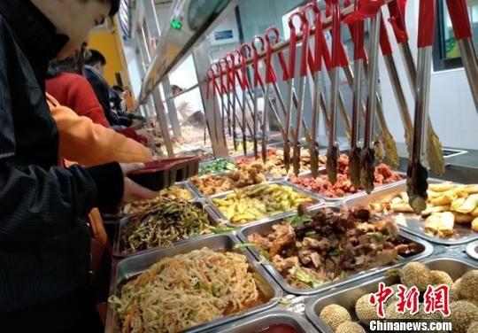 """西北师范大学西苑餐厅近期推出了一款""""智能选餐""""模式,有60多种大江南北的菜品通过""""无人结算""""供师生自由选择。图为11月11日,师生在智慧食堂里自主选餐。 冯志军 摄"""