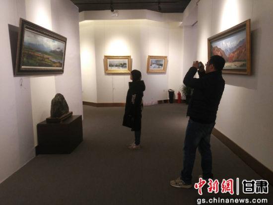 图为单国栋的油画同时也吸引着年轻人前来观看。