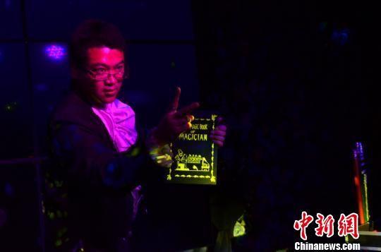 """甘肃""""90后""""魔术师金林表演魔术:打开字典扉页,变出花朵。 崔琳 摄"""