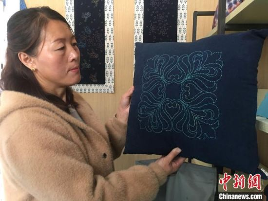 云田镇三十里铺村民王彩琴手提已完成的刺绣茶几垫到作坊领取手工费,她向记者展示绣娘们制作的刺绣抱枕。 张婧 摄