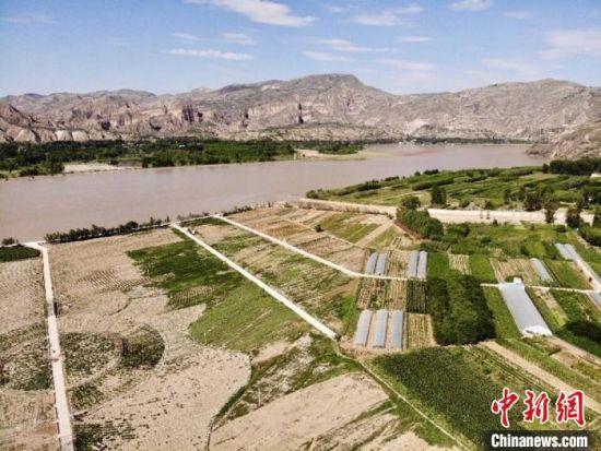 图为坐落在黄河之畔的甘肃临夏州积石山县,航拍境内三二家村的农业观光示范园。 高莹 摄