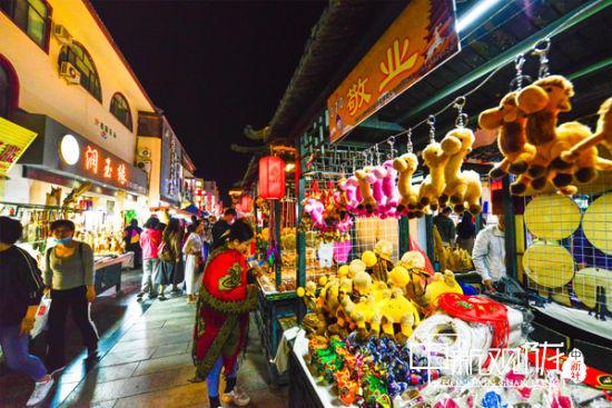 9月16日晚,游客正在敦煌夜市�x�敦煌旅游工�品。