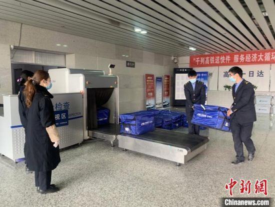 """20日晚,中国铁路兰州局集团有限公司服务""""双11""""电商黄金周运输的列车""""收官""""。图为工作人员搬运快递过安检。 董娜 摄"""