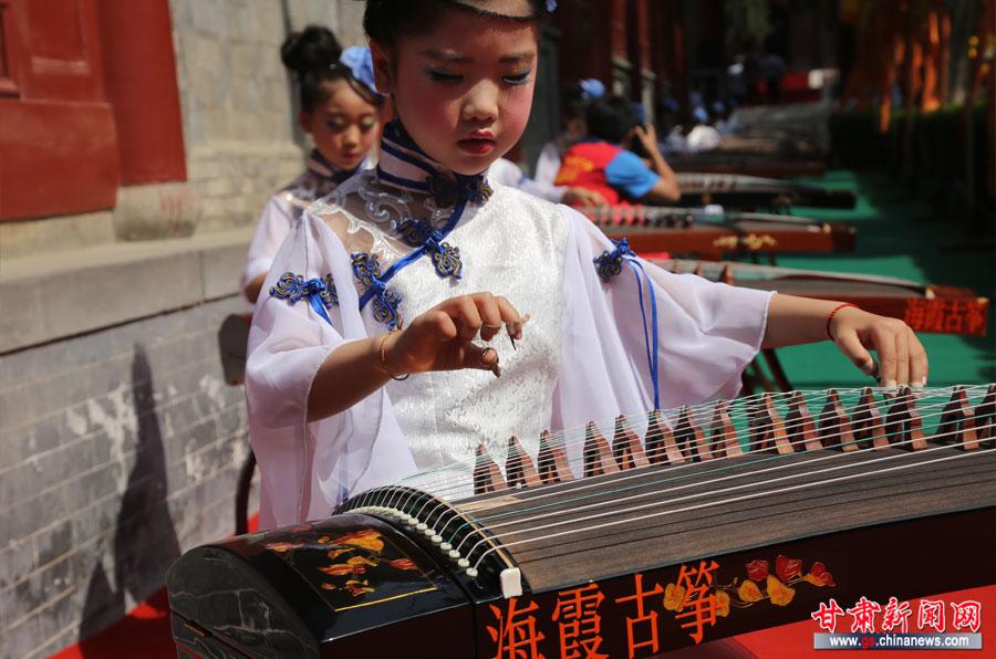 身穿传统服装的儿童在伏羲庙内弹奏古筝